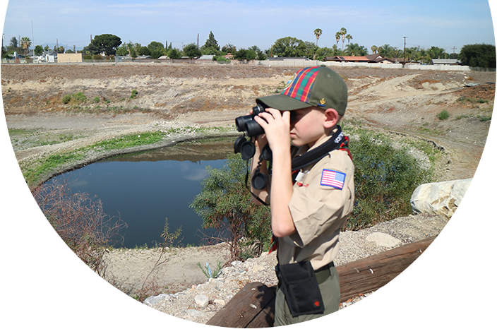 Boy Scout surveying a percolation basin with binoculars